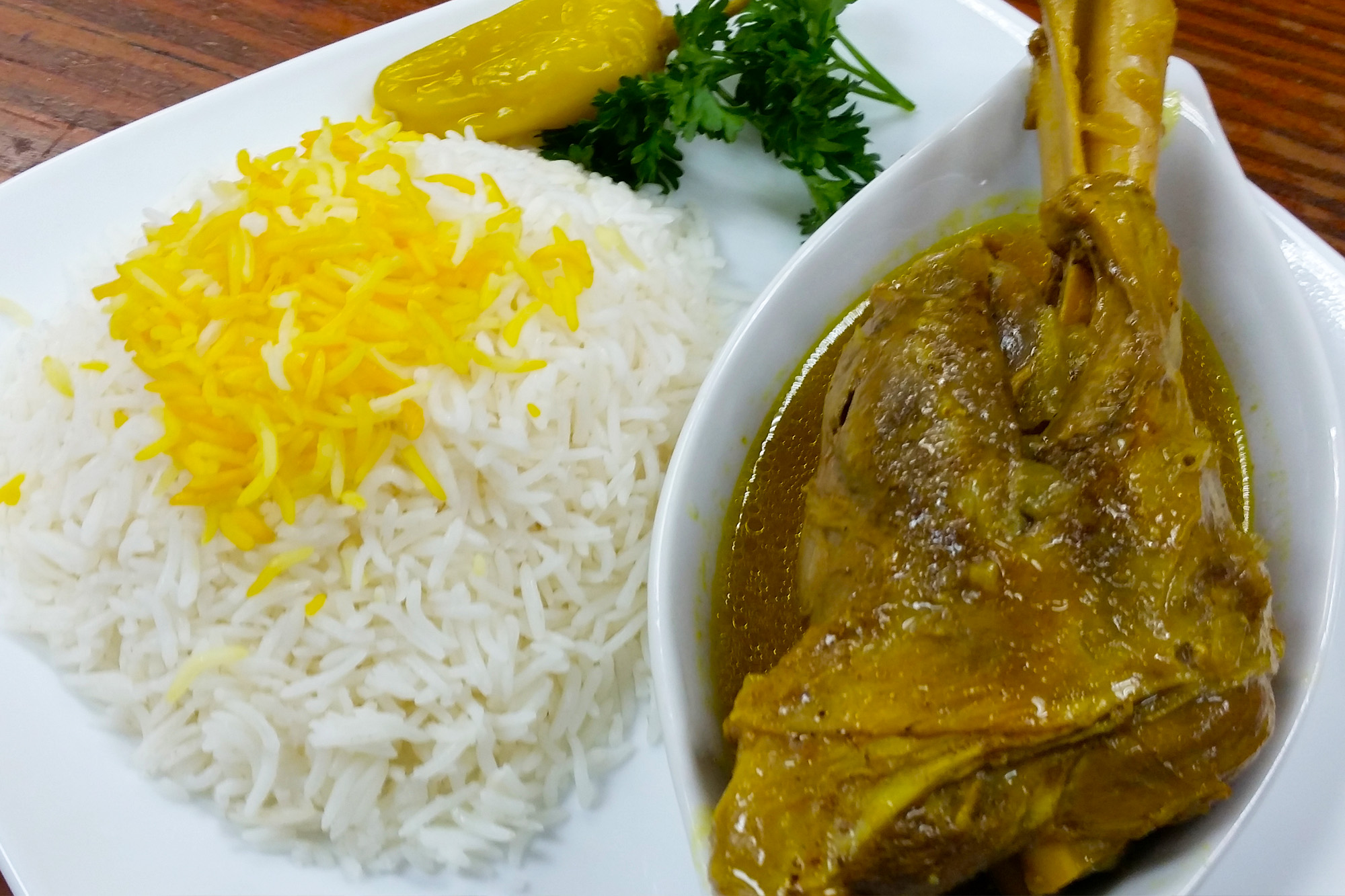 Lamb Shank slowly cooked and served with rice, dill weeds, and lima beans at Sahel Persian Restaurant