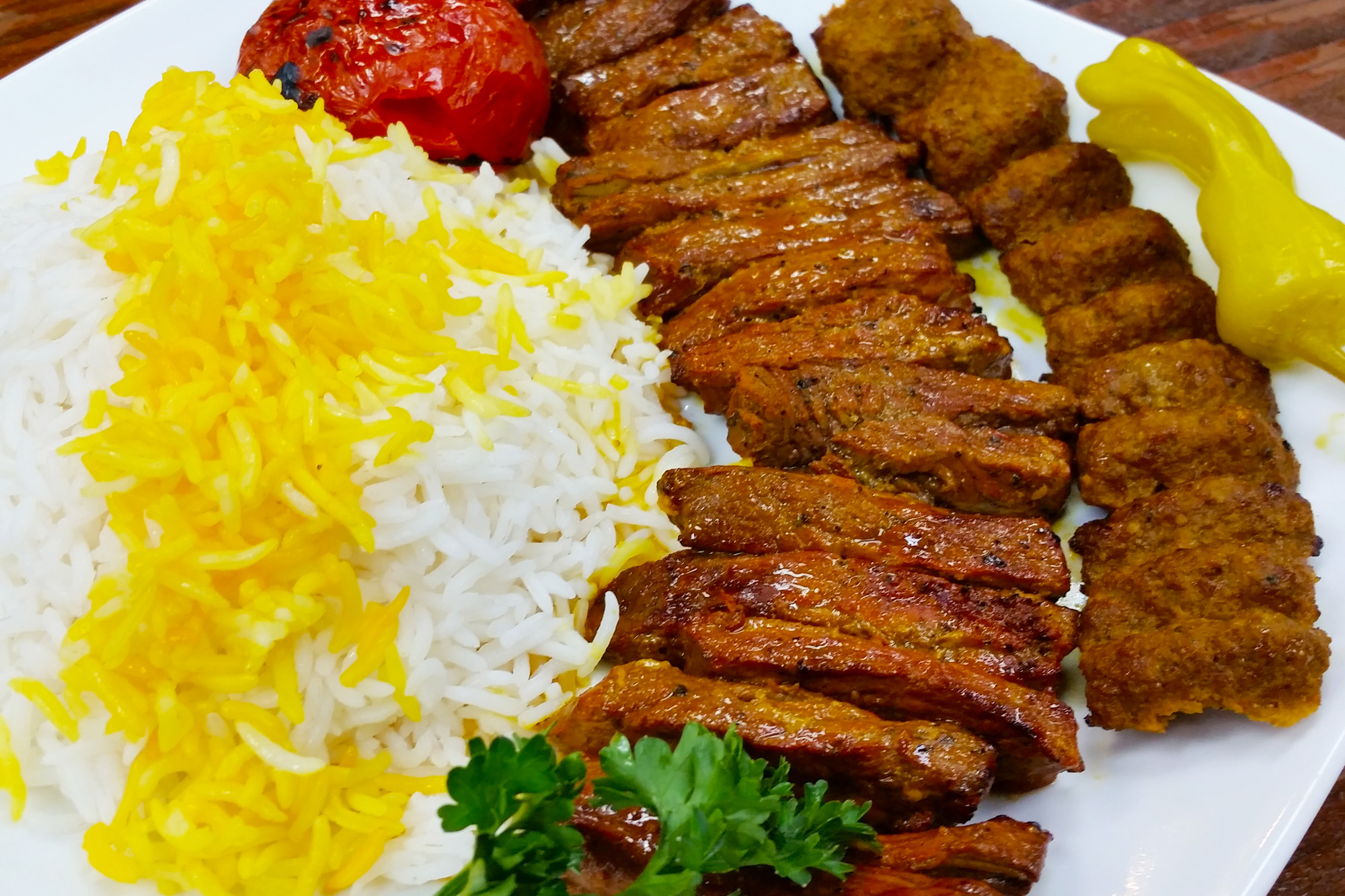 Soltani Kebab = One skewer of steak and one skewer of ground beef served with basmati rice and grilled tomatoes at Sahel Persian Restaurant
